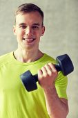 sport, fitness, lifestyle and people concept - smiling man with dumbbell flexing biceps in gym