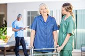 Female nurse assisting senior woman to walk with Zimmer frame at nursing home