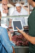 Cropped image of couple with digital tablet at butchery counter