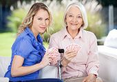 Portrait of smiling granddaughter and grandmother playing cards at nursing home porch