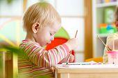 image of kindergarten  - smiling kid boy painting at home or playschool or kindergarten - JPG