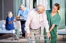 foto of nursing  - Happy female caretaker assisting senior man in using Zimmer frame at nursing home yard - JPG
