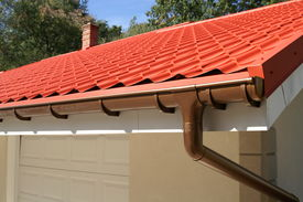 foto of red roof  - a corner of a house with gutters and metal roof - JPG