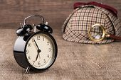picture of private investigator  - Deerstalker or Sherlock Hat and magnifying glass on Old Wooden table - JPG