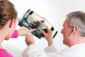 Dentista explicando o raio-x para o paciente
