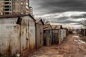 pic of spayed  - Old metal garages sprayed with urban paints sit underneath dark grey spring skies  - JPG