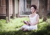 stock photo of gothic girl  - Beautiful young gothic girl in white shirt with book outdoor - JPG