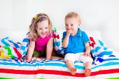 stock photo of little young child children girl toddler  - Two kids sleeping in bed under colorful blanket - JPG