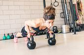 image of kettles  - woman making push ups on the kettle bells in a gym - JPG