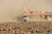 pic of plowing  - Farmer using a disc cultivator to break of soil after plowing on a field in Oregon - JPG