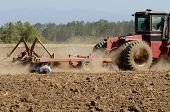 image of plowing  - Farmer using a disc cultivator to break of soil after plowing on a field in Oregon - JPG