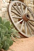 stock photo of wagon wheel  - wooden wagon wheel beside stone building and green cactus