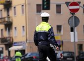 image of policeman  - Italian policeman in uniform while blocking traffic with the Red paddle to block cars - JPG