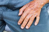stock photo of lap  - close up of elderly male hand on his lap - JPG