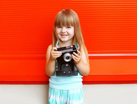 stock photo of little girls photo-models  - Portrait of little girl child with old retro vintage camera against the colorful red wall - JPG