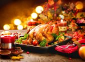 Roasted Turkey. Thanksgiving table served with turkey, decorated with bright autumn leaves and candl poster