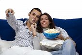 stock photo of watching movie  - young couple watching tv at home and laughing - JPG