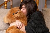 Young Woman Embracing And Kissing Teddy Bear Sitting On Sofa Close-up