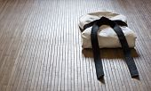stock photo of taekwondo  - judo gi with black belt on bamboo carpet - JPG