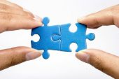stock photo of reunited  - hands holding two jigsaw puzlle for joining - JPG