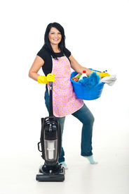 stock photo of house cleaning  - Cheerful woman with pink apron preparing for cleaning house with vacuum cleaner and holding a blue basin with cleaning products - JPG