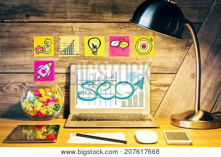 poster of Creative designer desktop with table lamp SEO sketch on laptop scree various devices and stickers with rocket icons on wooden wall. SEO and media concept
