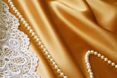 Beautiful cultured pearls and embroidered lace on elegant gold satin background.  Macro with shallow dof.