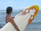 image of breather  - a woman surfer takes a breather with her surfboard and watches the water - JPG