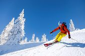 Skier Skiing Downhill In High Mountains Against Blue Sky poster