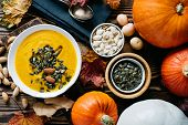 Autumn pumpkin soup with pumpkin seeds and almond, shot from above rustic wooden table poster
