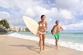 Hawaii Waikiki beach surfers having fun going surfing. Multiracial couple running out of water with  poster