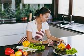 Young Happy Woman In Apron Looking At Recipe In Tablet In The Kitchen. Vegetable Salad. Diet. Dietin poster