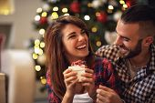 Cheerful couple with gift in hands enjoying together on Christmas eve  poster