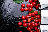 Scattered Cherry From Enamel Cups. Cherries In Iron Cup On Black Background. Healthy, Summer Fruit. poster