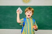 Happy Kid Playing With Paper Airplane In Classroom. Boy With Origami Plane In Primary School. Back T poster
