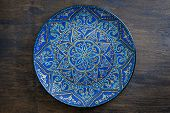 Decorative Ceramic Plate With Blue And Golden Colors, Painted Plate On Wooden Background, Closeup. D poster