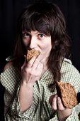 Retrato de una mujer de mendigo pobre comer pan en sus manos