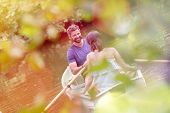 Tilt shot of happy mid adult couple boating in lake during summer poster