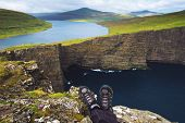 Legs Of Hiker Sitting On Top Of A Cliff With Views Over Cliff Traelanipan And Lake Sorvagsvatn Locat poster