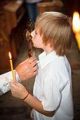 Постер, плакат: Маленький мальчик целуя крест в церкви