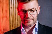 A close up portrait of a brutal handsome man in glasses. Mens beauty, fashion. Optics for men. poster