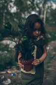 A Homeless Girl Is Standing On A Garbage Dump With A Houseplant In A Pot. The Concept Of Environment poster