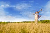 stock photo of hands-free  - Man worshiping god shot at yellow grass - JPG