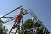 Young Man On A Ladder Is Erecting A Stage With A High Truss For A Music Festival Against A Blue Sky poster