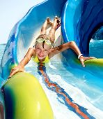 picture of amusement park rides  - Child on water slide at aquapark - JPG