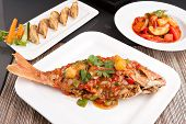 stock photo of red snapper  - Freshly prepared Thai style whole fish red snapper dinner with sweet and sour shrimp and pan fried gyoza dumplings appetizer - JPG