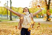 season and people concept - happy young woman throwing maple leaves and having fun in autumn park poster