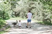 Father And A Little Son Are Walking In The Forest With A Dog.a Dog And A Human.  A Dog Is A Best Fri poster