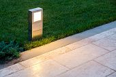 Ground Lantern Lighting Marble Walkway In The Evening Park With A Green Lawn, Closeup Lantern Illumi poster
