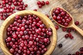 Fresh Red Forest Cranberry In A Round Bowl With A Wooden Spoons On A Wooden Table Surface. poster